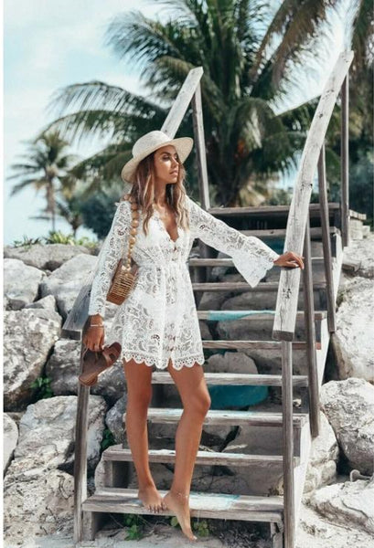 Girl standing on staircase wearing the Janina Lace Beach Cover Up, straw hat and carrying a bag and slippers.