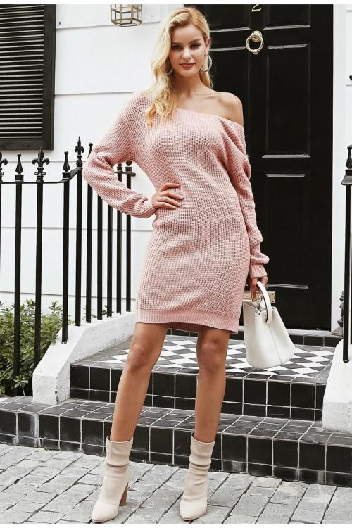 Girl striking a pose wearing pink Mica Knitted Sweater Dress, white hand bag and nude boots.