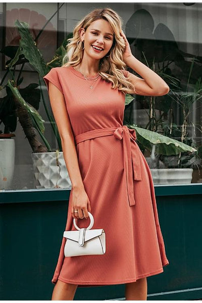 Girl wearing the pink Sommer Tie-Waist Midi Dress, gold jewelries and white hand bag.
