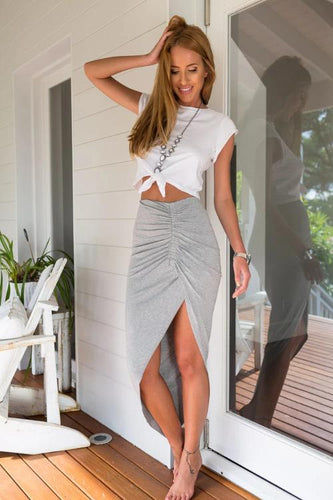 Girl wearing the gray Estrella Asymmetrical Slit Skirt, white top and jewelries.