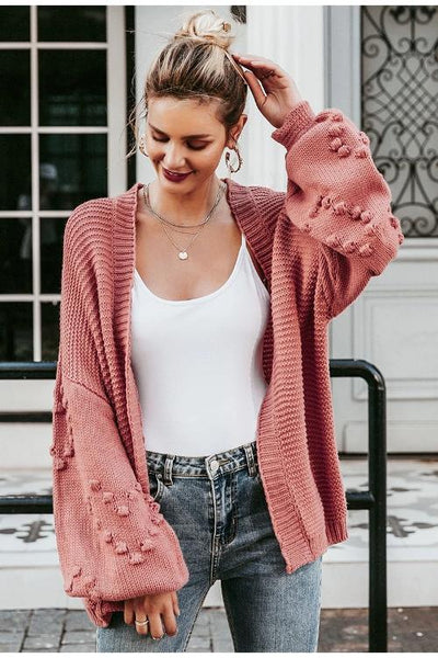 Girl wearing pink Nely Oversized Knitted Cardigan, white tank top, jeans and hair tied in a bun.