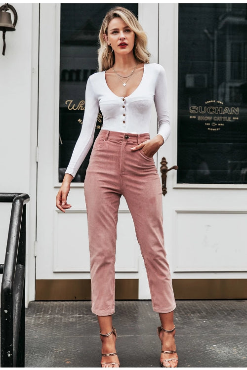 Girl wearing the rose color Firefly Corduroy Pants, white long sleeve top, gpld jewelries and gold straps sandals.
