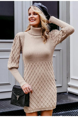 Girl wearing the khaki Clariz Cable Knit Sweater Dress, black shoulder bag, black beret hat and dangling earrings.