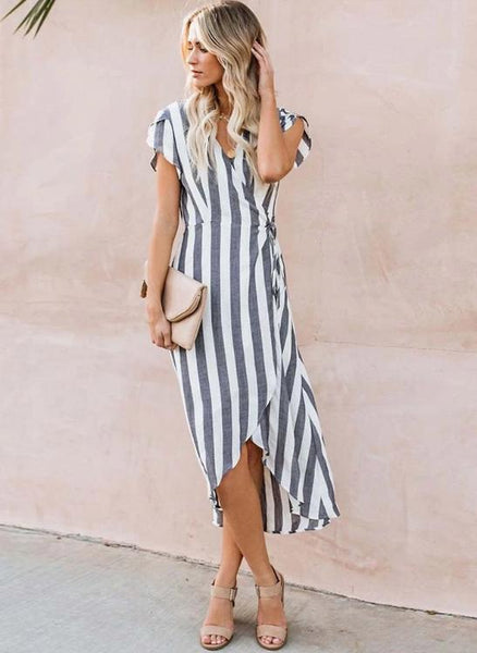 Girl wearing the recy Stripe Wrap Dress, nude clutch and nude sandals.