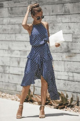 Girl wearing the blue Adira Polka Dots Dress, beige sandals, sunglasses and white clutch.