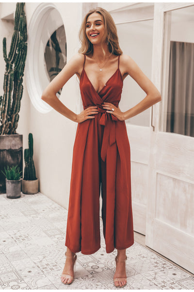 Girl wearing the Tory Brick Red Jumpsuit, clear straps sandals and dainty jewelries.