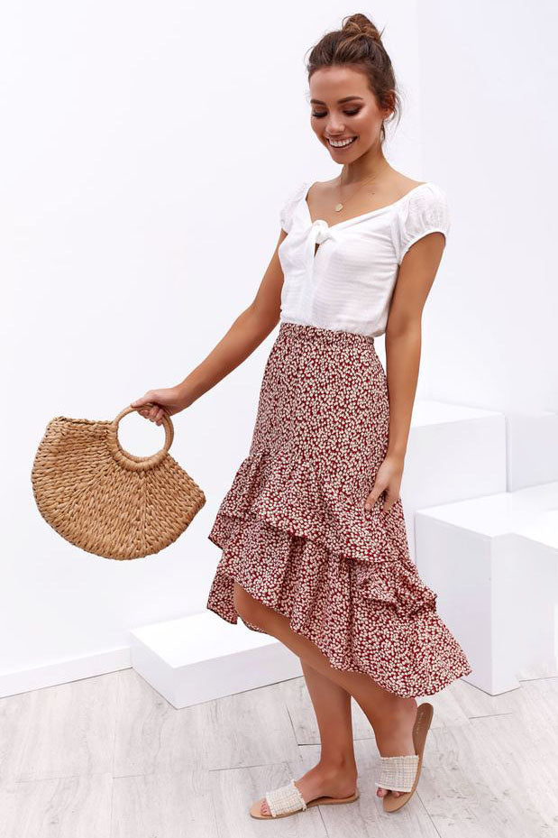 Girl wearing the red Leona Asymmetrical High Waist  Skirt, white top, dainty jewelries, woven hand bag and neutral color slides.