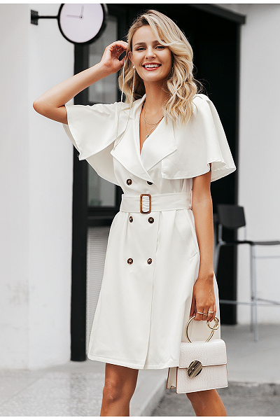 Girl wearing the white Reese Trench Dress, white hand bag with gold handle, layed gold necklaces and hair clip.