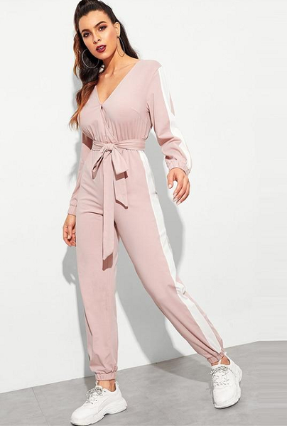 Girl wearing the Reina Belted Pink Jumpsuit, big hoop earrings and white sneakers.