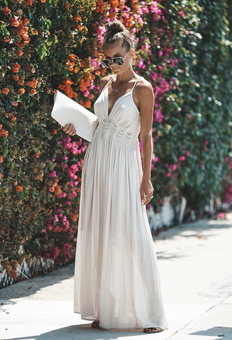 Girl wearing the white Shaina Halter Maxi Dress, white clutch bag, sunglasses and boho jewelries.