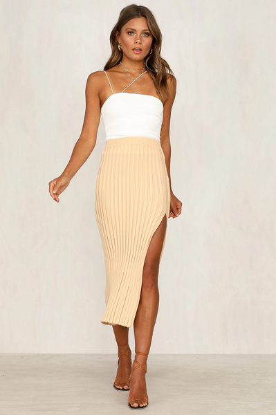 Girl wearing the beige Tandi Ribbed Midi Skirt, white tank top, nude sandals and boho jewelries.