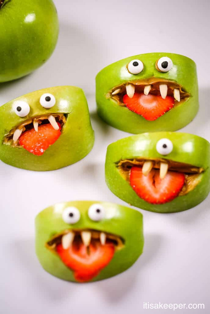 Healthy Halloween monster snacks made from apples, strawberries, nuts and peanut butter