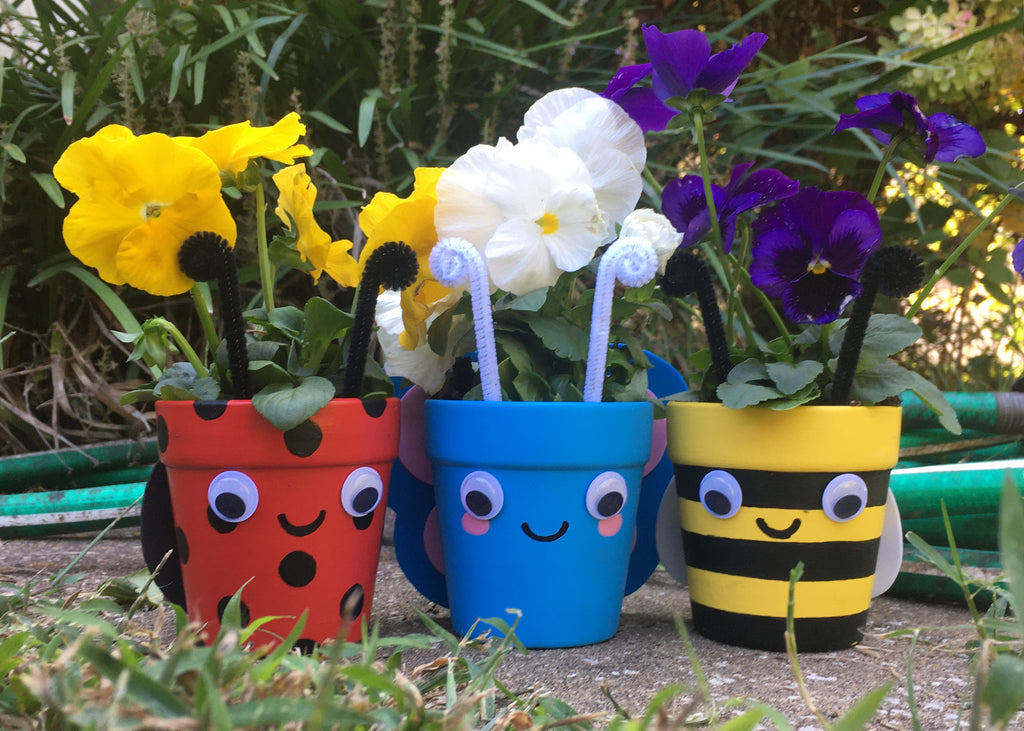 three flower pots painted to look like a ladybug light blue butterfly and a bumblebee with googly eyes and yellow and black white and purple pansies planted in them