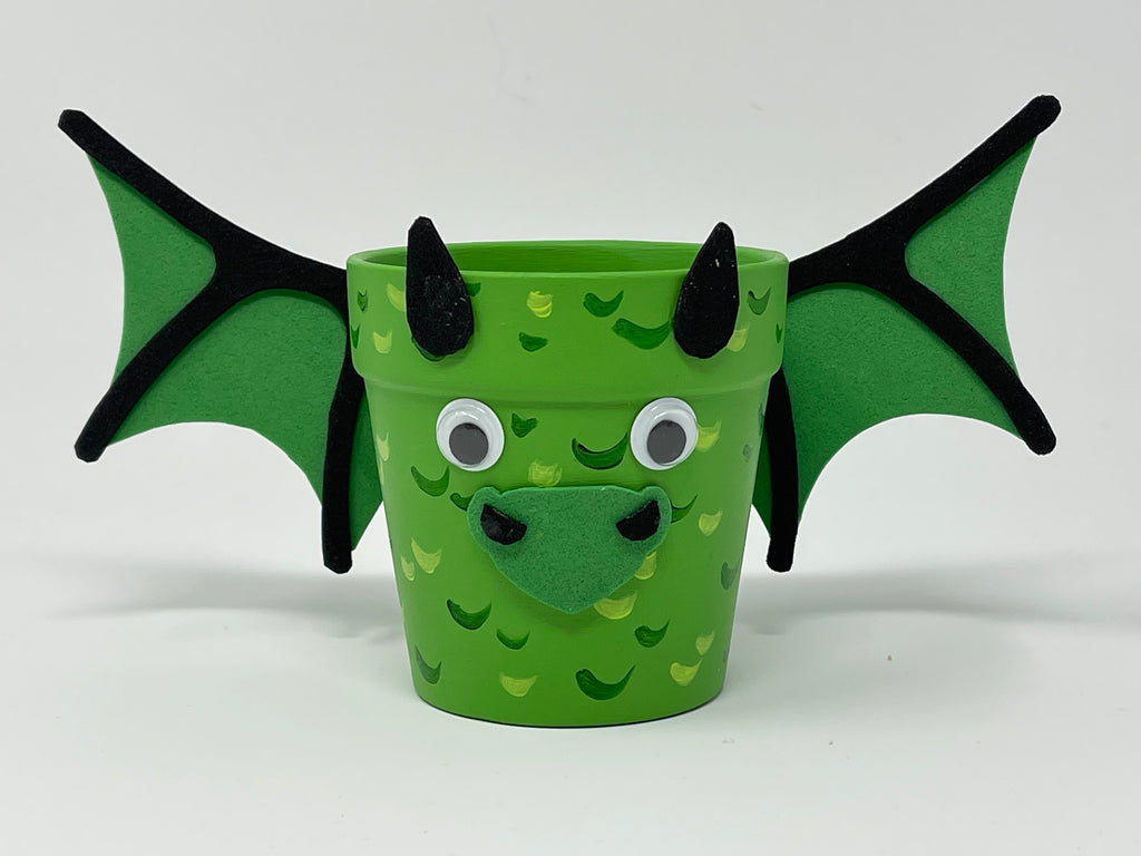 Small flower pot painted to look like a green dragon using foam pieces for wings horns and mouths and googly eyes and painted scales