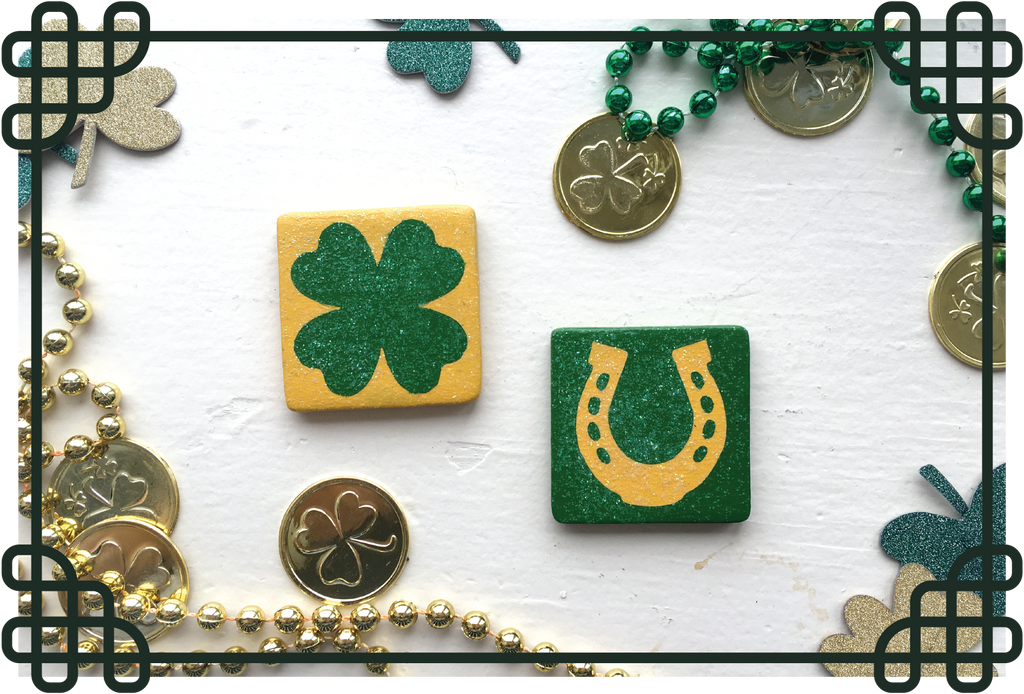 Two square tiles laying on white background, one painted with a green four leaf clover on yellow, the other painted with a yellow horseshoe on green, both with a coating of glitter. On counter around tile are fake gold coins, green and gold plastic beaded necklaces, and glittery green and gold shamrock paper cutouts. Entire image is encased in Celtic knot border.