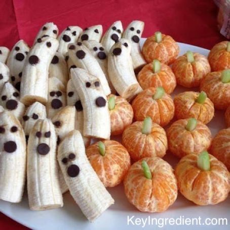 Healthy fruit snacks made to looks like ghosts and pumpkins being served for Halloween guests