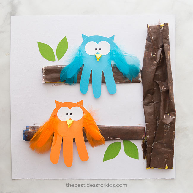 Adorable handprint cutouts decorated like owls using feathers and google eyes to decorate in fall themes for Thanksgiving