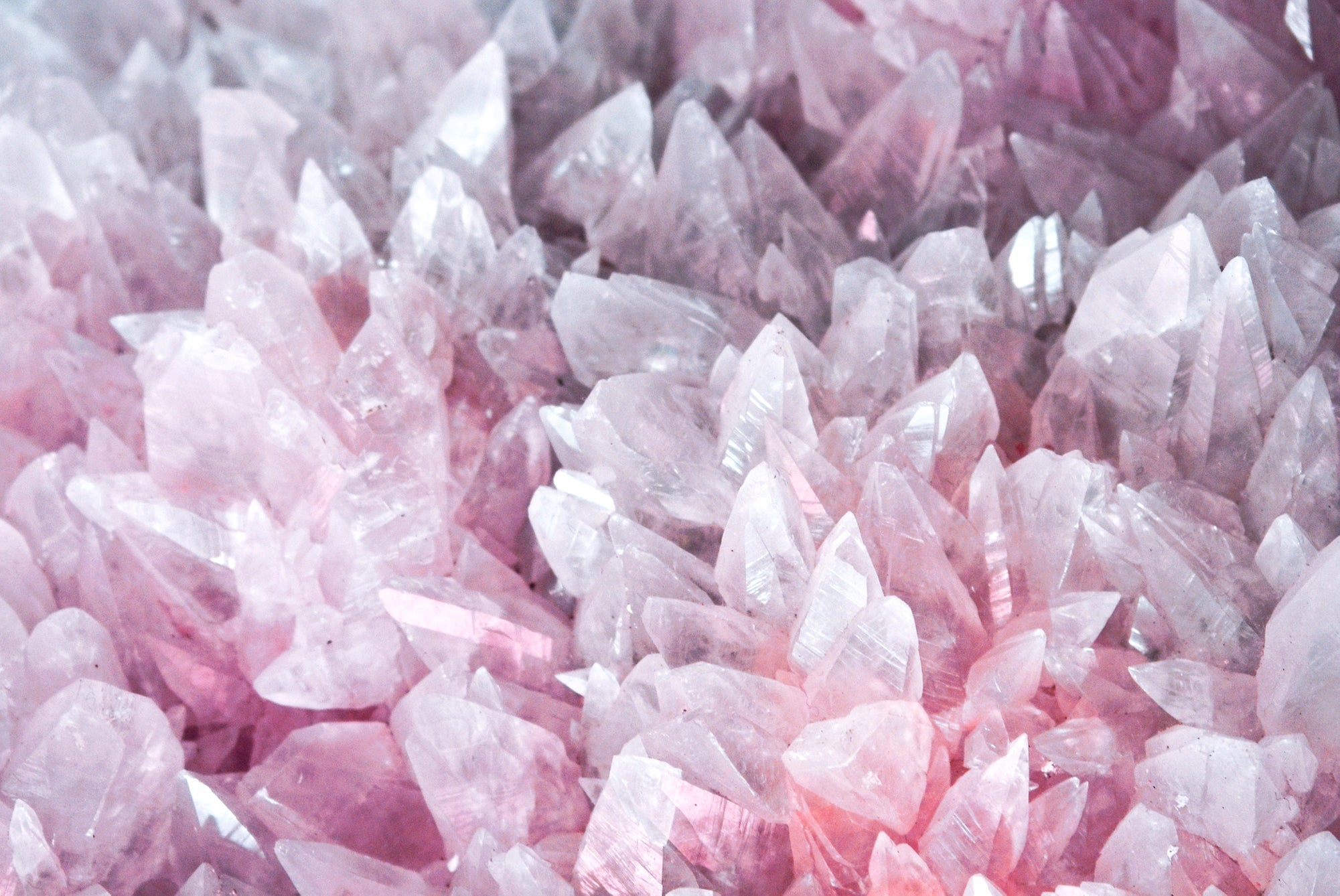 Close up of pale pink and grey crystal clusters muck like the inside of a geode