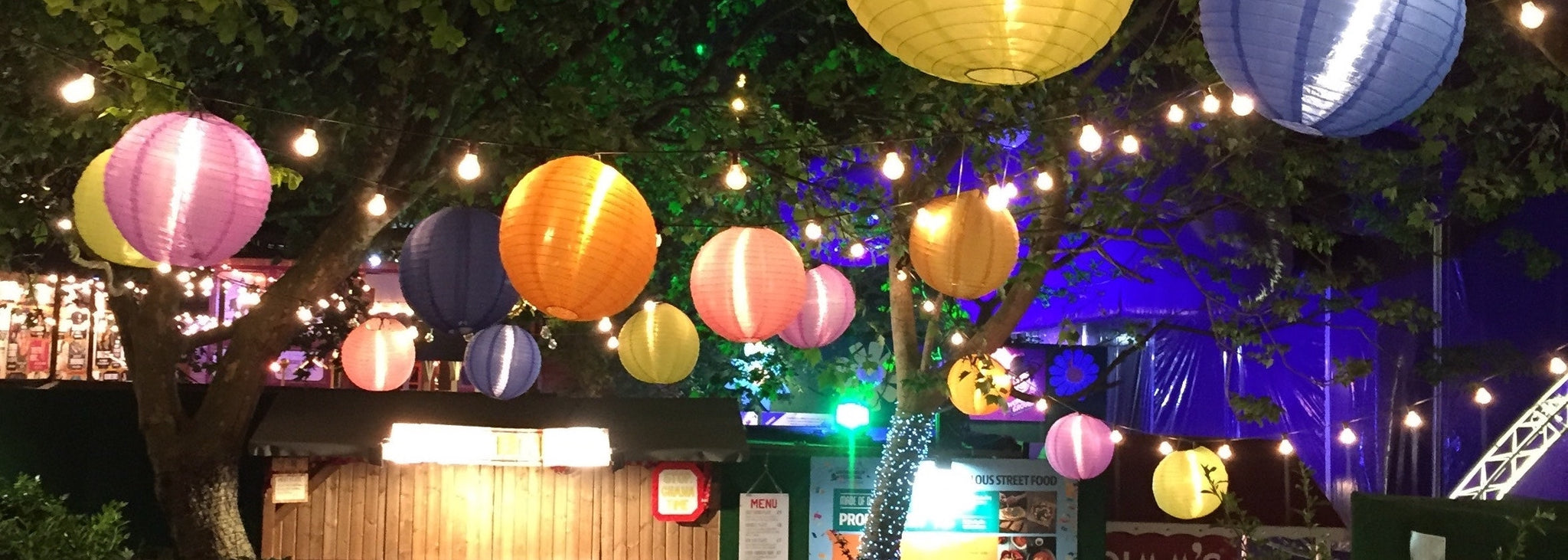 Multicolor paper lanterns hung from trees and lit up after dark