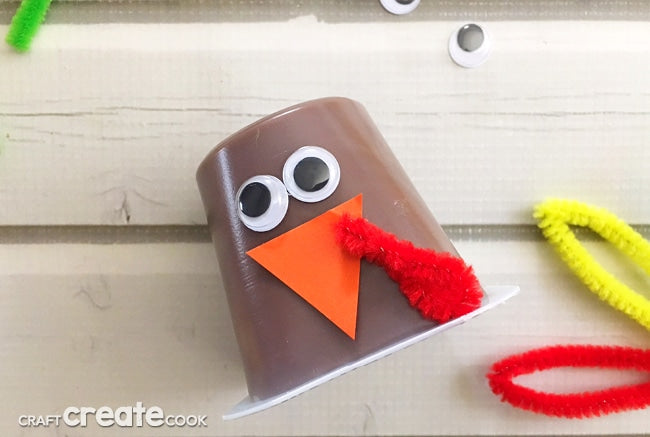 Chocolate pudding cup decorated to look like a turkey for Thanksgiving using craft foam, google eyes, and pipe cleaners