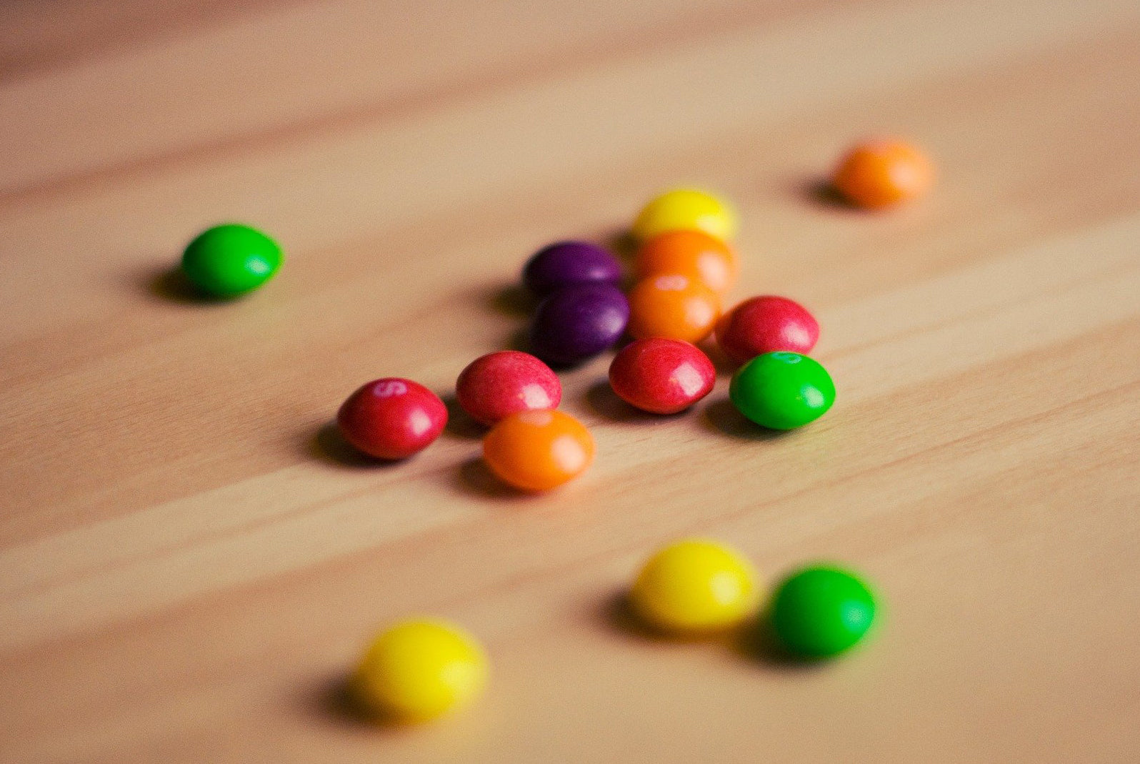 a few skittles candies in a variety of colors spread out across a light wooden surface