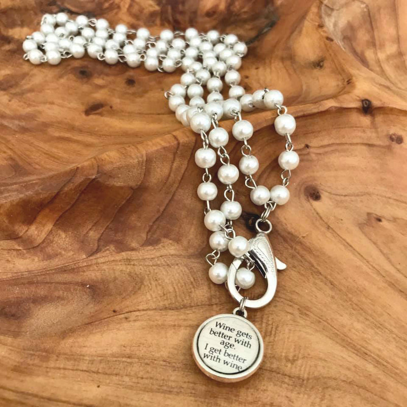 This 36 inch necklace has ivory colored pearls and a double sided pendant that says