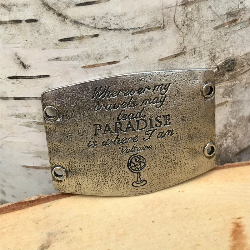 "Antique brass finish Lenny & Eva bracelet sentiment that reads, ""Wherever my travels may lead, paradise is where I am."" Quote by Voltaire. Globe design etched under the quote."