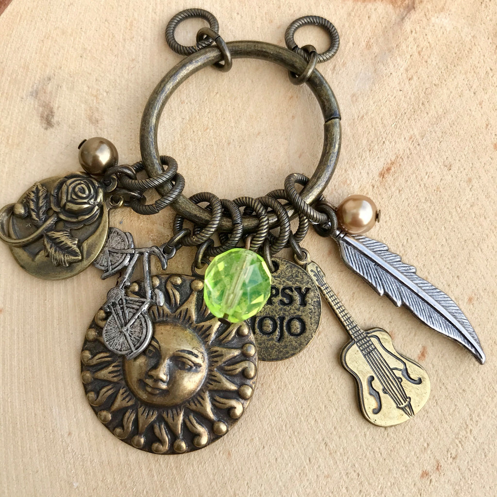 Antique brass Gypsy Mojo pendant with rose, bicycle, sun, guitar, feather, and colored bead charms