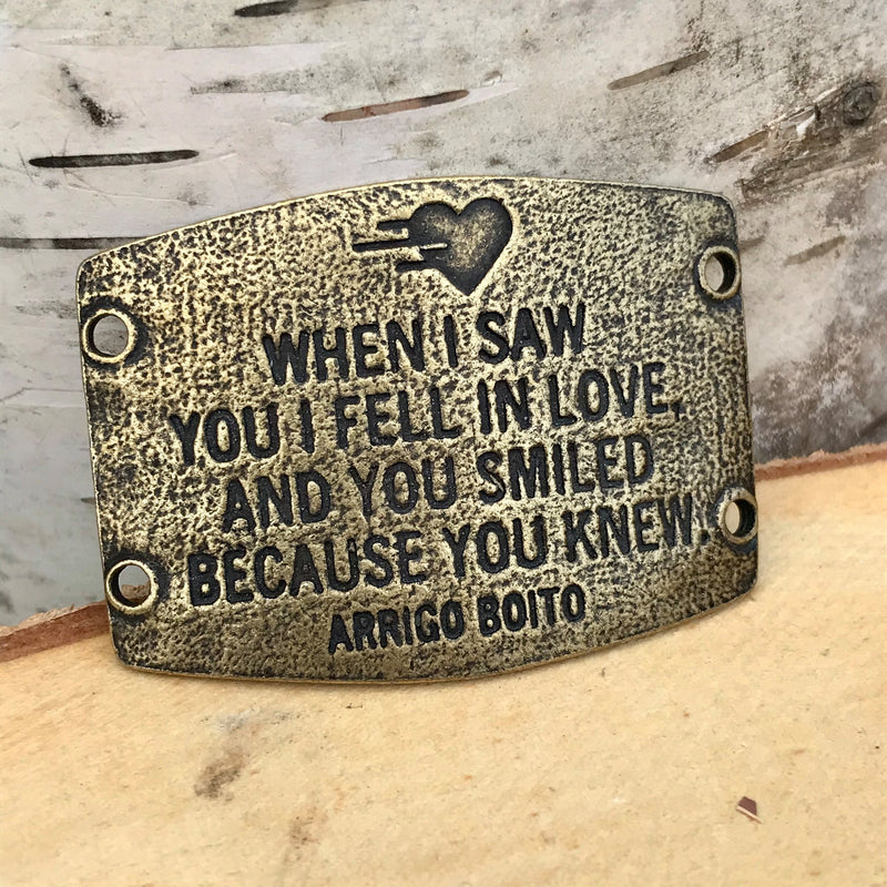 "Antique brass finish Lenny & Eva bracelet sentiment that reads, ""When I saw you I fell in love, and you smiled because you knew."" Quote by Arrigo Boito. A heart etching is above the quote."