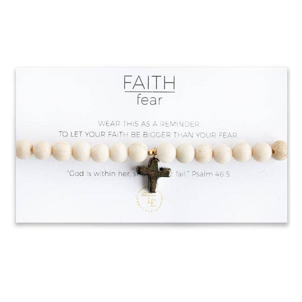 "Ivory color beaded stretch bracelet with a pyrite cross charm. Card states, ""Wear this as a reminder to let your faith be bigger than your fear."" and ""God is within her, she will not fail."" Psalm 46:5"