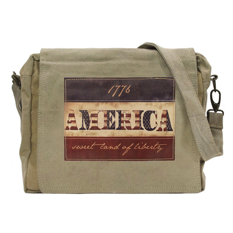 "Tan or olive (colors vary) crossbody bag made of recycled military tents. This bag features a large patch on the flap that reads ""America...sweet land of liberty"" Patch has a red, white and blue themed background."