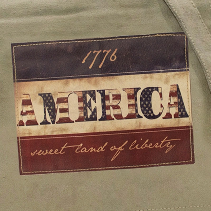"Closeup of the red, white and blue colored ""America...sweet land of liberty"" patch on the flap of the crossbody bag made of recycled military tents."