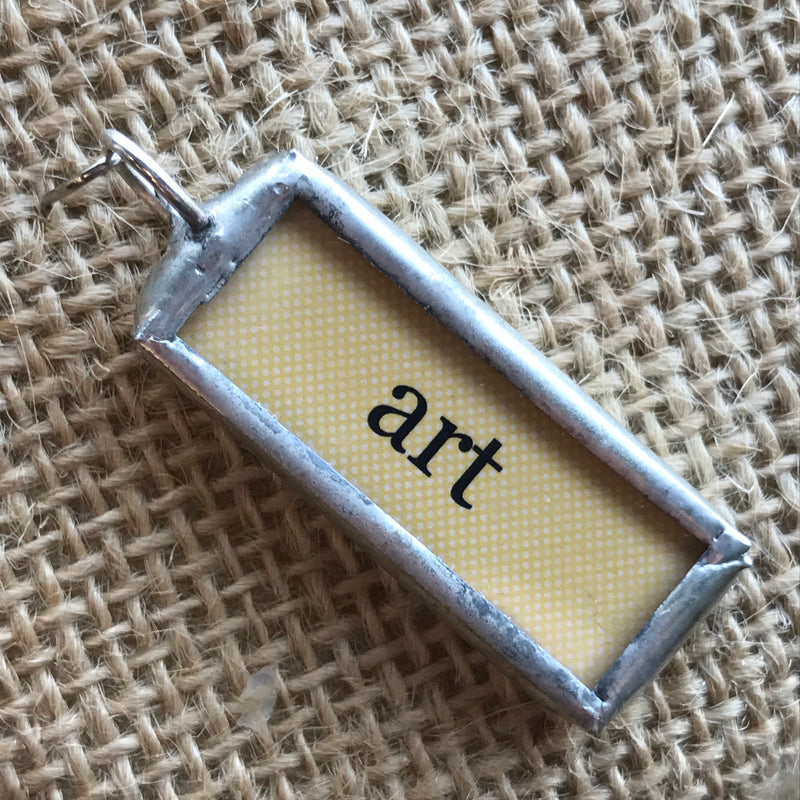 "Necklace pendant with a yellow background and the word ""art"""