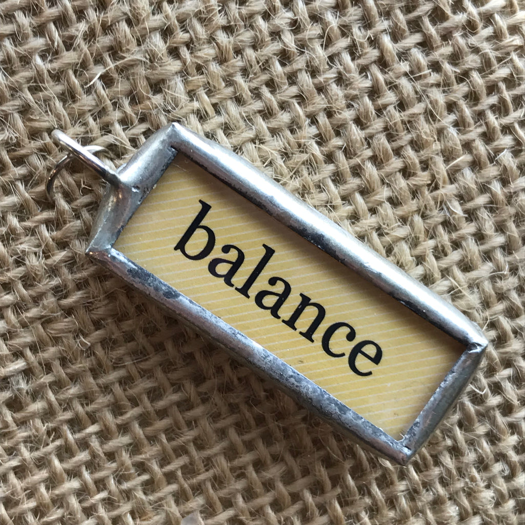 "Soldered necklace pendant with a yellow background and the word ""balance"""