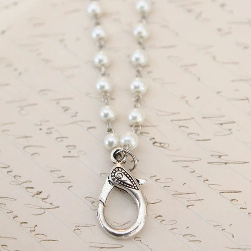 White pearl necklace with a silver lobster clasp to add charms to