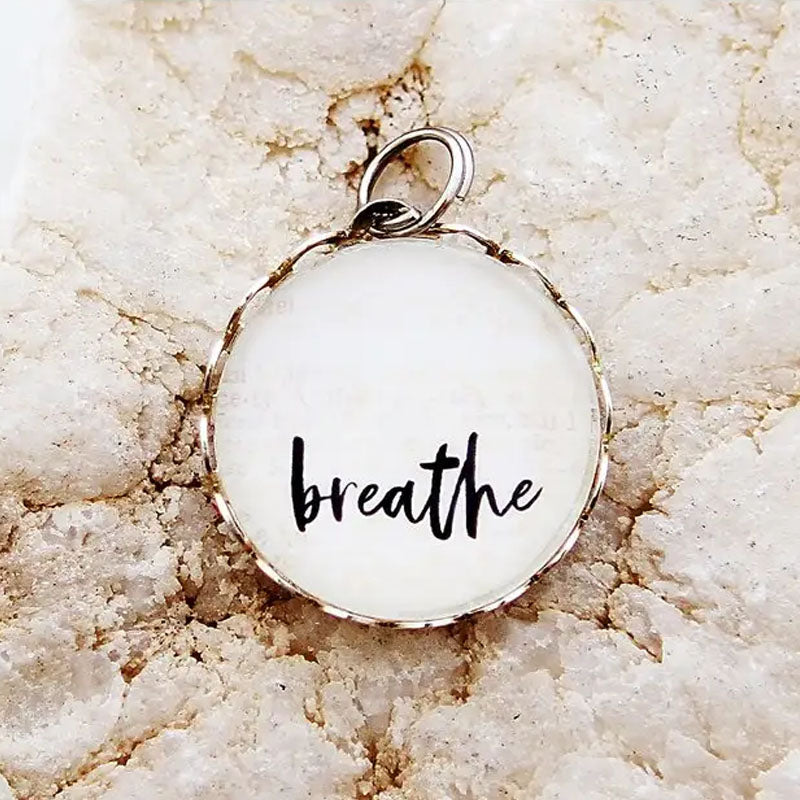 "Round necklace pendant with the word ""breathe"" on a white background."