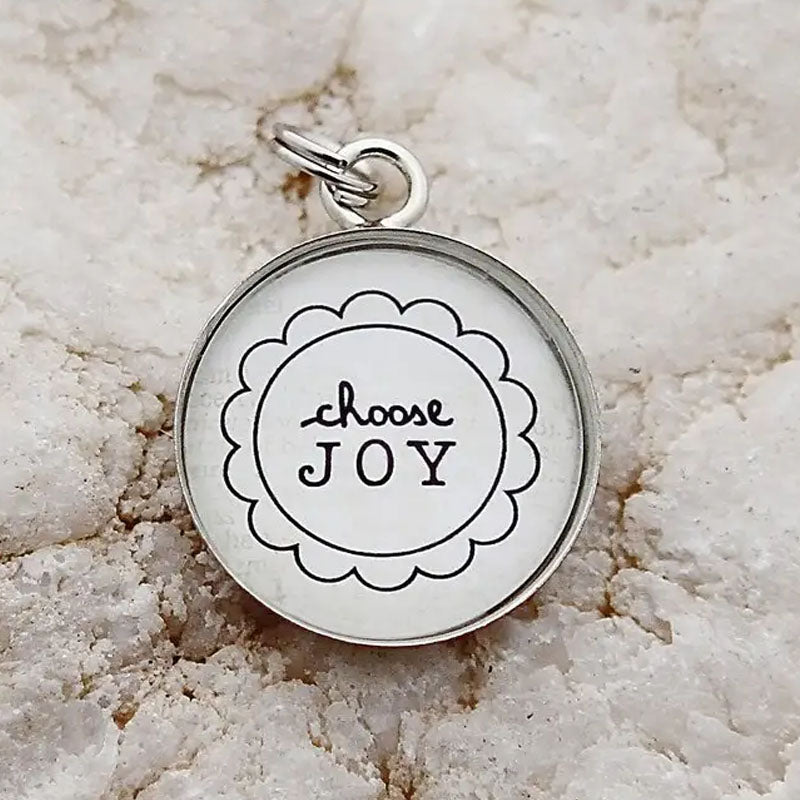 "Round necklace pendant with the words ""choose joy"" inside a flower design."