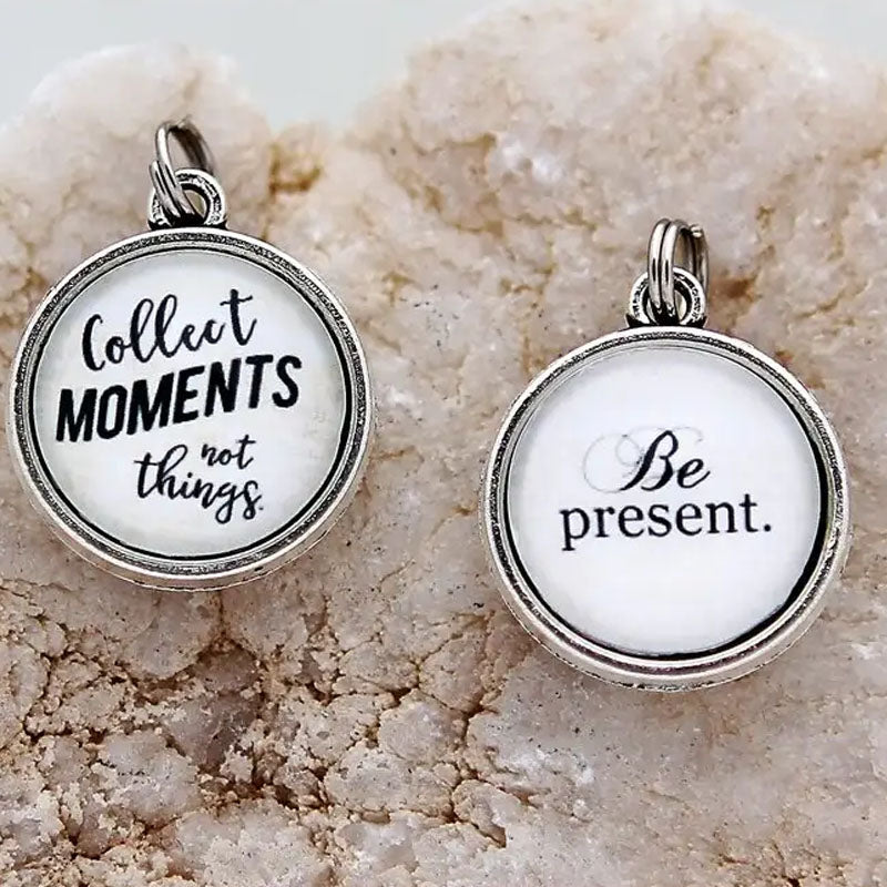 "Necklace pendant with the text ""Be Present"" on one side and ""Collect moments not things."" on the other side"