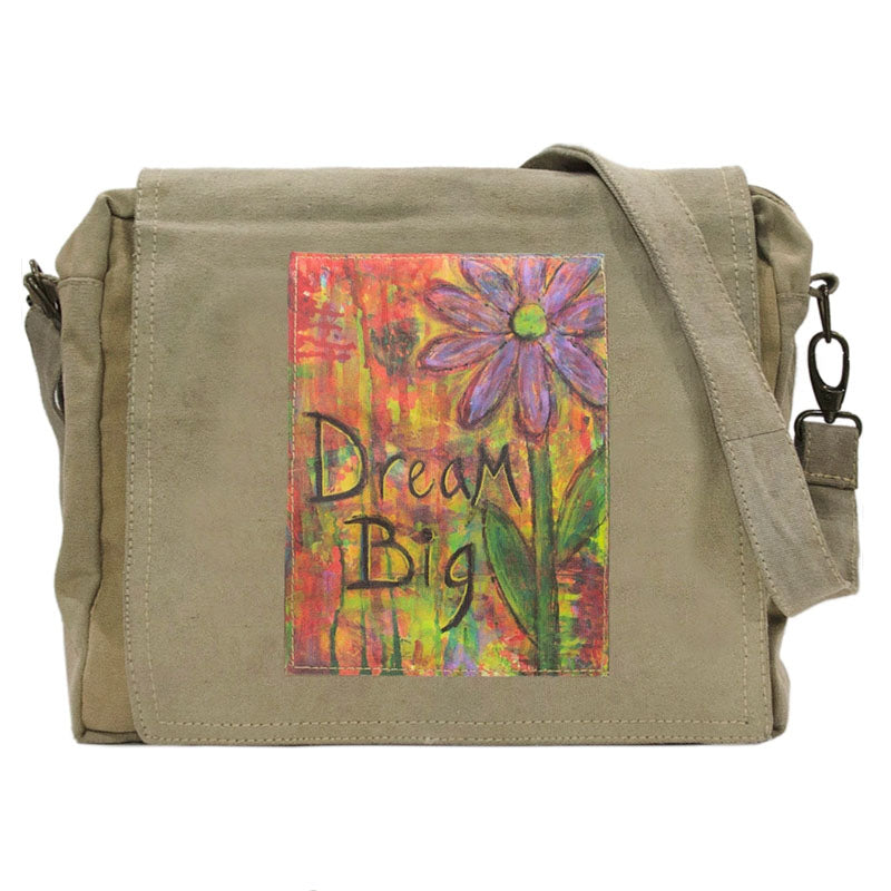 "Tan or olive (colors vary) crossbody bag made of recycled military tents. This bag features a large colorful patch on the flap that reads ""Dream Big"" Patch has a brightly colored background with a purple flower."