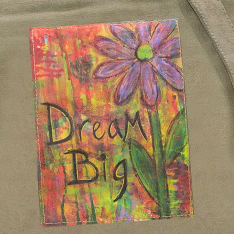 "Closeup of the brightly colored ""Dream Big"" patch on the flap of the crossbody bag made of recycled military tents."