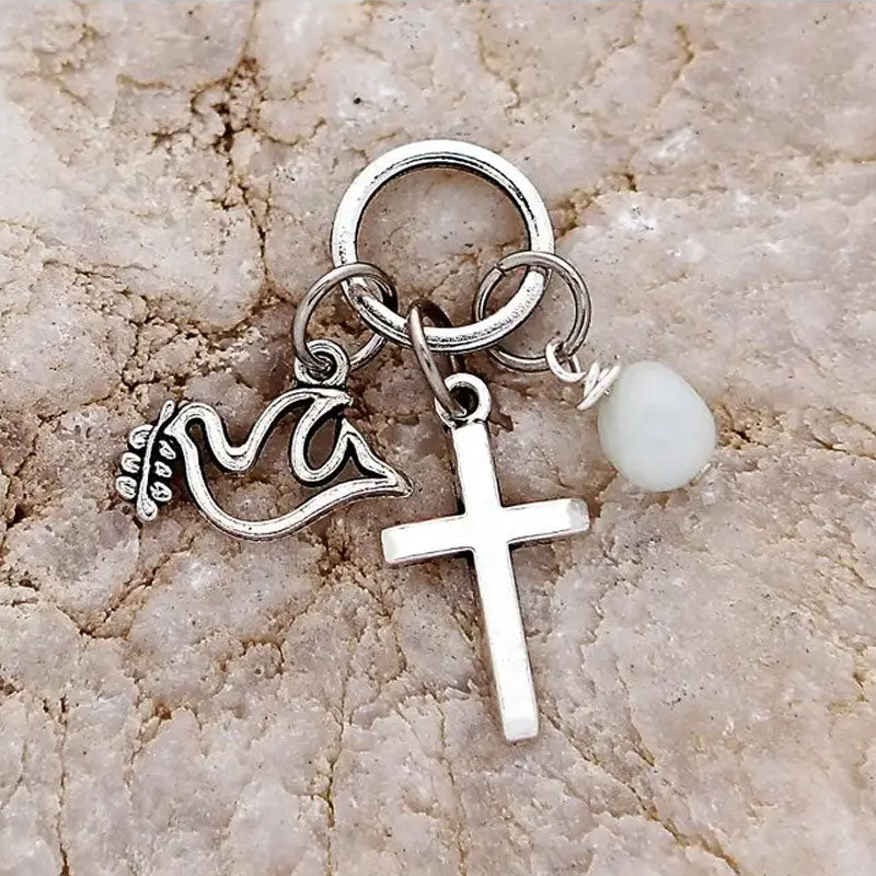 A silver cross, dove, and pale aqua colored stone hang off this silver plated ring.