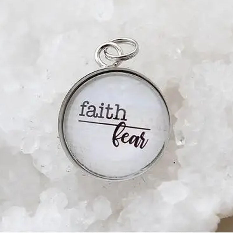 Round necklace pendant with faith above a line and fear below it.