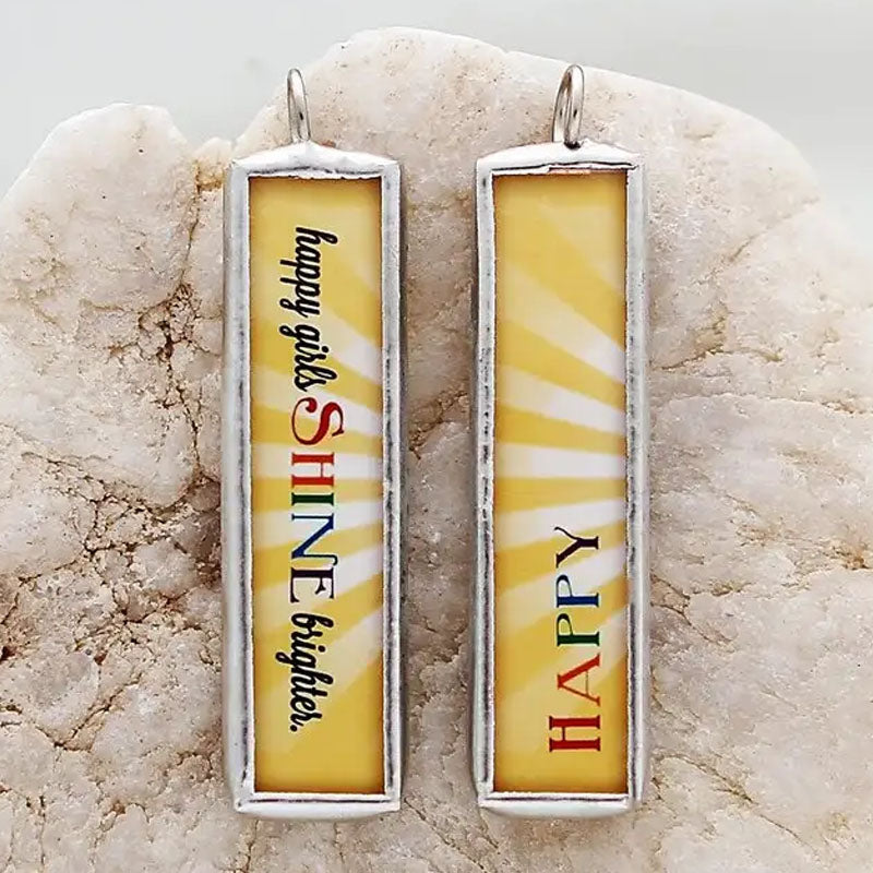 "Reversible necklace pendant with a yellow background and the word ""happy"" on one side and ""happy girls shine brighter"" on the reverse."