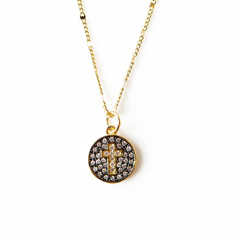 Gold necklace with a circle pendant that features a rhinestone cross surrounded by rhinestones on a black background.