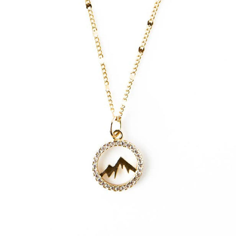 Gold plate necklace chain with a small white rhinestone circle pendant that has a gold toned mountain in the center.
