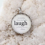 "Round necklace pendant with a white background and silver metal edge. Text on pendant reads ""smile live joyfully laugh a little every day"""
