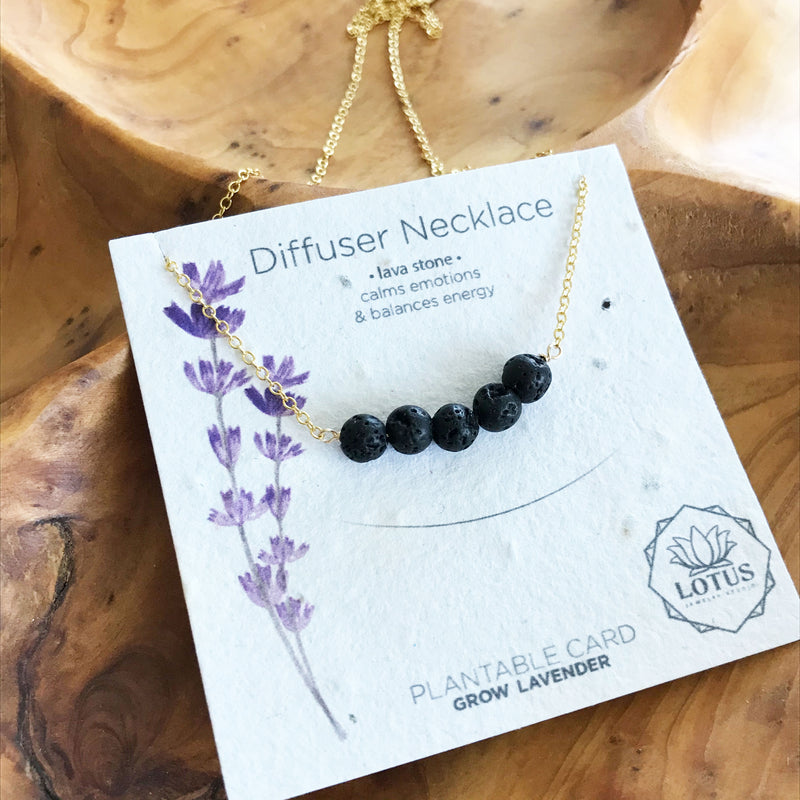 Gold filled necklace with black lava rocks for essential oil aromatherapy. Made in the U.S.A. by Lotus Jewelry Studio. Jewelry card contains lavender seeds and can be planted.