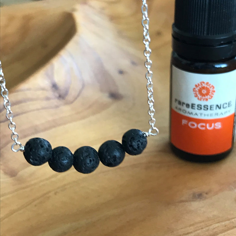 Sterling silver necklace with a band of black lava rocks to diffuse your favorite essential oils. Pictured with Focus essential oil by rareESSENCE. Made in the U.S.A. by Lotus Jewelry Studio.