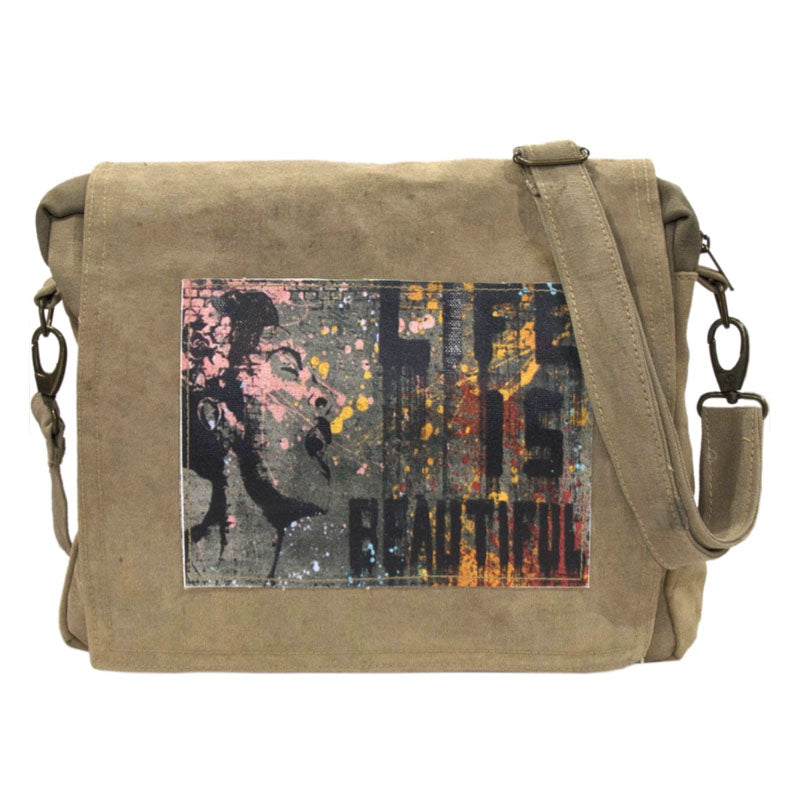 "Tan or olive (colors vary) crossbody bag made of recycled military tents. This bag features a large colorful patch on the flap that reads ""Life is beautiful"" Patch has a gray background adorned with pink, yellow and red streaks and the image of a woman."