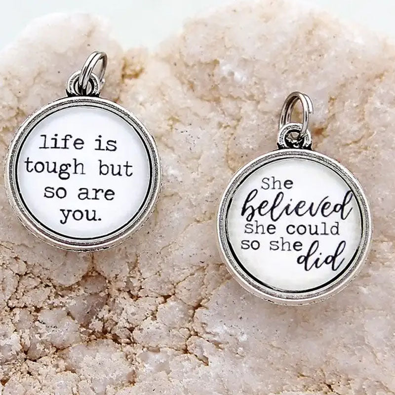 "Necklace pendant with the text ""life is tough but so are you"" on one side and ""she believed she could so she did"" on the reverse"